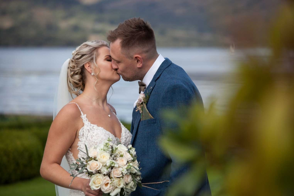 Bride and Groom kiss at Inn On The Lake in Ullswater